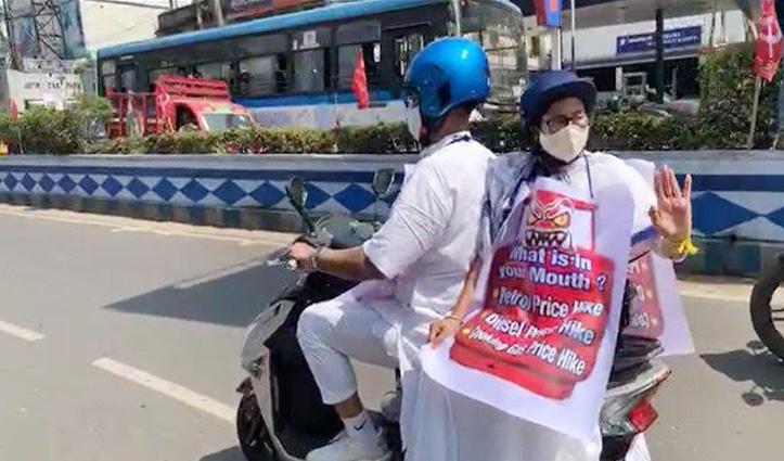 """Petrol-Diesel की बढ़ती कीमतों के खिलाफ """"दीदी"""" का प्रदर्शन, E-Bike पर बैठकर गले में लटकाया पोस्टर"""